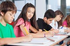 Adolescente que se sienta con los compañeros de clase que escriben en Fotos de archivo