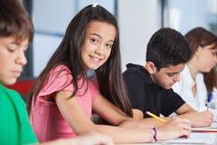 Adolescente que se sienta con los compañeros de clase que estudian en Imágenes de archivo libres de regalías