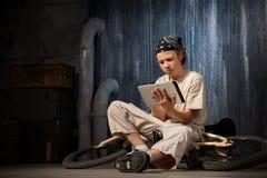 Adolescente que se sienta con PC de la tableta Imágenes de archivo libres de regalías