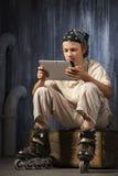 Adolescente que se sienta con PC de la tableta Fotografía de archivo