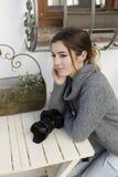 Adolescente que se sienta con su cámara de la foto en la tabla Fotos de archivo