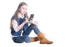 Adolescente que se sienta con un teléfono Fotografía de archivo