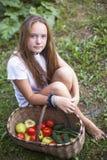 Adolescente que se sienta con una cesta de verduras Jardín Foto de archivo