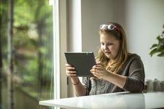 Adolescente que se sienta con una tableta cerca de la ventana en casa Foto de archivo