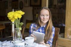Adolescente que se sienta con una tableta en la cafetería E-libros de la lectura Fotos de archivo libres de regalías