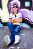 Adolescente que se sienta contra la pared de la pintada Imagen de archivo libre de regalías