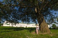 Adolescente que se sienta debajo de un árbol y de libros leídos Fotos de archivo libres de regalías