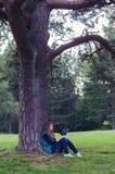 Adolescente que se sienta debajo del libro del árbol y de lectura Imagenes de archivo