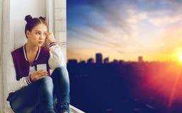 Adolescente que se sienta en alféizar con smartphone Fotos de archivo libres de regalías