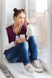 Adolescente que se sienta en alféizar con smartphone Imagen de archivo libre de regalías