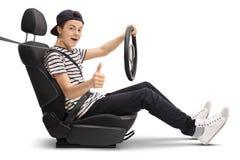 Adolescente que se sienta en asiento de carro y que da el pulgar para arriba Fotografía de archivo libre de regalías
