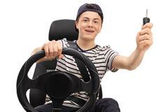 Adolescente que se sienta en asiento de carro y que lleva a cabo llave del coche Imagen de archivo