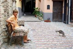 Adolescente que se sienta en banco en la ciudad histórica Fotos de archivo