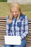 Adolescente que se sienta en banco en parque con el ordenador portátil Fotos de archivo libres de regalías
