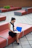 Adolescente que se sienta en banco y que lee algo Fotografía de archivo libre de regalías