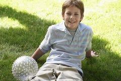 Adolescente que se sienta en césped con una bola Foto de archivo libre de regalías
