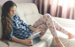 Adolescente que se sienta en casa con una PC de la tableta Imagen de la forma de vida de la muchacha de pelo largo caucásica herm imagenes de archivo