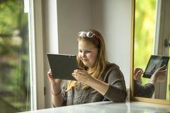Adolescente que se sienta en casa con una tableta hospitalidad Imagenes de archivo