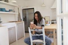 Adolescente que se sienta en cocina usando el smartphone, vista delantera Fotos de archivo libres de regalías