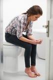 Adolescente que se sienta en cuarto de baño con la prueba de embarazo Fotografía de archivo libre de regalías