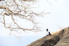 Adolescente que se sienta en el acantilado Fotos de archivo