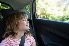 Adolescente que se sienta en el asiento trasero del coche Imagenes de archivo