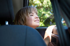 Adolescente que se sienta en el asiento trasero del coche Fotografía de archivo
