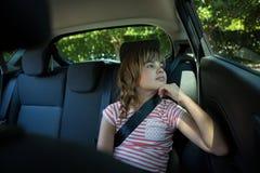 Adolescente que se sienta en el asiento trasero del coche Fotografía de archivo libre de regalías