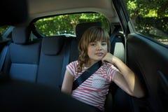 Adolescente que se sienta en el asiento trasero del coche Fotos de archivo
