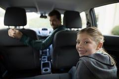 Adolescente que se sienta en el asiento trasero mientras que mujer que conduce un coche Foto de archivo libre de regalías