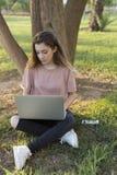 Adolescente que se sienta en el césped con un ordenador portátil Imagenes de archivo