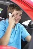 Adolescente que se sienta en el coche, hablando en el teléfono celular Imagen de archivo