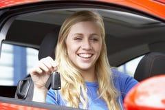 Adolescente que se sienta en el coche, llevando a cabo claves del coche Imagenes de archivo