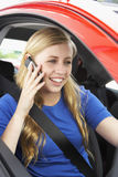 Adolescente que se sienta en el coche que habla en el teléfono celular Fotografía de archivo libre de regalías