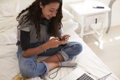 Adolescente que se sienta en el envío de mensajes de texto de la cama, visión elevada Fotos de archivo