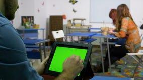 Adolescente que se sienta en el escritorio en sitio de clase y que birla la exhibición de una PC de la tableta metrajes