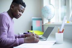 Adolescente que se sienta en el escritorio que hace la asignación de la preparación en el ordenador portátil foto de archivo