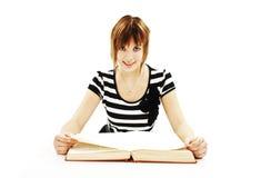 Adolescente que se sienta en el escritorio y el libro de lectura Imagen de archivo