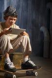 Adolescente que se sienta en el monopatín Fotos de archivo libres de regalías
