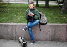 Adolescente que se sienta en el parapeto con el teléfono móvil Imágenes de archivo libres de regalías