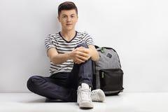 Adolescente que se sienta en el piso al lado de una mochila Imagen de archivo