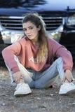 Adolescente que se sienta en el piso delante de un coche Imagen de archivo libre de regalías