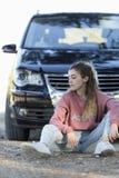 Adolescente que se sienta en el piso delante de un coche Foto de archivo libre de regalías