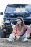 Adolescente que se sienta en el piso delante de un coche Fotos de archivo libres de regalías