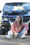 Adolescente que se sienta en el piso delante de un coche Foto de archivo