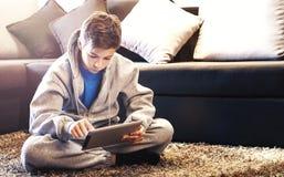 Adolescente que se sienta en el piso en el cuarto Imagen de archivo