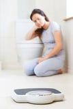 Adolescente que se sienta en el piso que mira básculas de baño Fotos de archivo