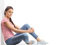 Adolescente que se sienta en el piso y que se inclina contra una pared Fotografía de archivo libre de regalías