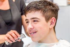 Adolescente que se sienta en el salón del peluquero para un corte de pelo Fotografía de archivo libre de regalías