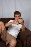 Adolescente que se sienta en el sofá Fotos de archivo